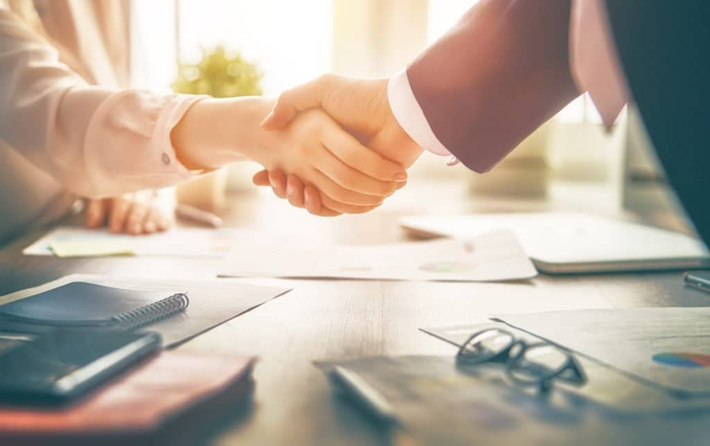 woman and man shaking hands over business paperwork